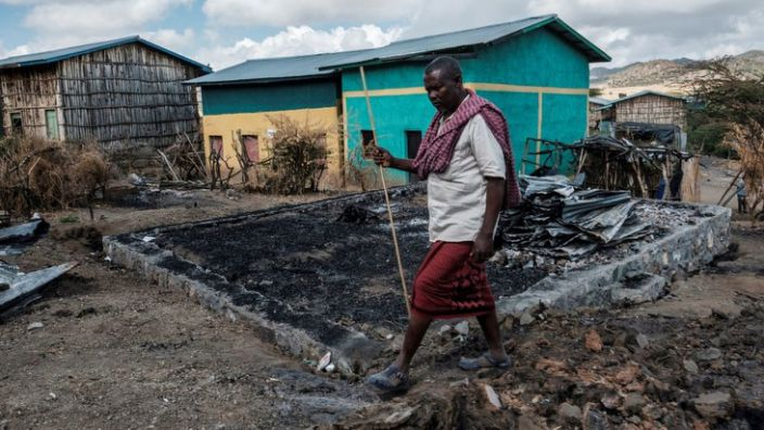 Addis Ceesay, 49, walks past his destroyed home in the village of Besoper, in the Tigray region of Ethiopia, December 9, 2020