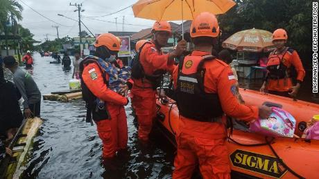 Rescuers evacuate people from a flooded residential area in Banjarbaru, South Kalimantan, Borneo Island, on January 17, 2021.