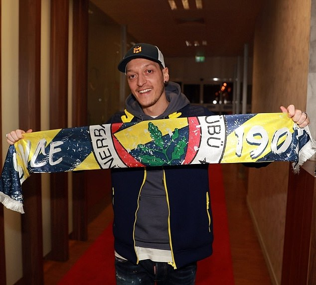 Mesut Ozil stands wearing a Fenerbahce scarf after landing in Istanbul on Sunday night